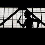 A member of a 1,600 meter relay team is silhouetted against a window at the Prince George's County Sports and Learning Complex Monday during the Maryland 1A-2A indoor track and field championships.